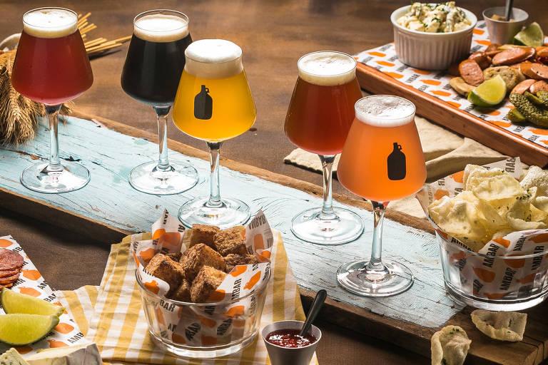 mesa com petiscos e copos cheios de chope do bar Ambar