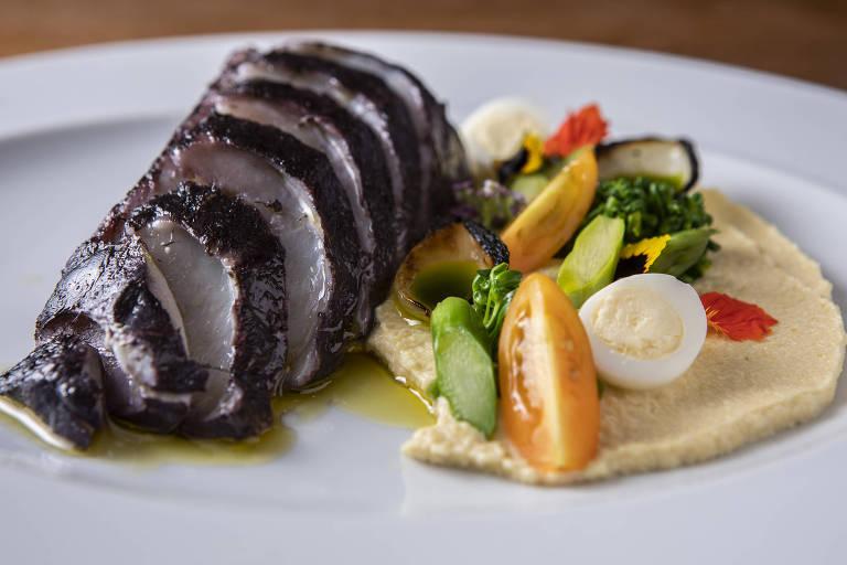 Bacalhau escuro com legumes no prato