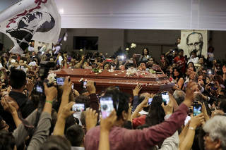 People react as the coffin holding the body of Peru's former President Alan Garcia arrives after Garcia fatally shot himself on Wednesday, in Lima