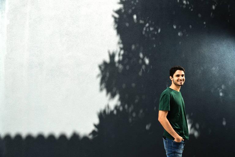 André posa voltado para o lado direito da foto, em frente a uma parece branca em que há a sombra da copa de uma árvore