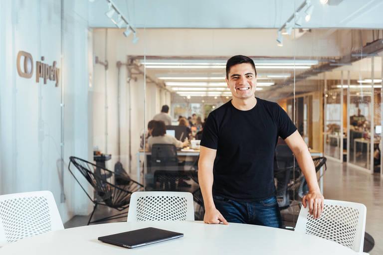 Alessio Alionço em pé, em sala com mesa, cadeiras brancas e paredes de vidro, através das quais dá para ver o escritório da empresa ao fundo