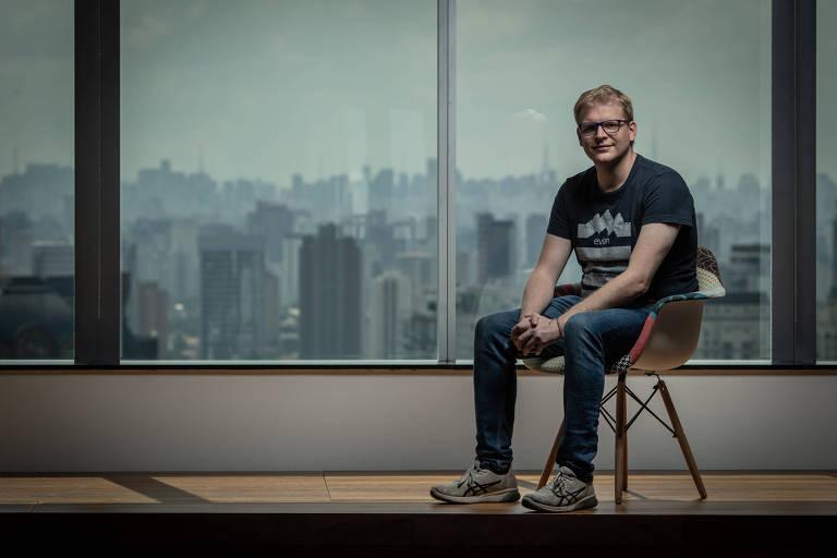 Thomas sentado em frente a uma janela com vista para prédios de São Paulo