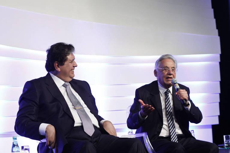 Os dois homens estão sentados em um palco, vestem ternos; FHC fala ao microfone e Alan Garcia o observa enquanto sorri