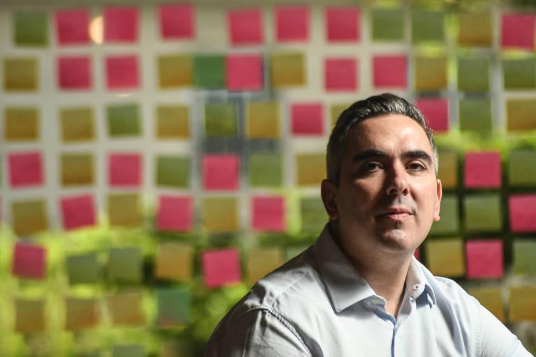 Rodrigo em frente a um vidro transparente cheio de post-its rosas e amarelos