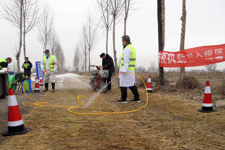 FILE PHOTO: Police officers and workers in protective suits are seen at a checkpoint on a road leading to a farm where African swine fever was detected, in Xushui