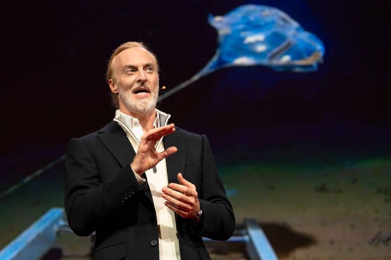 Victor Vescovo fala no TED 2019 em Vancouver; atrás dele, foto de possível nova espécie de água-viva que ele encontrou em suas expedições ao fundo do mar