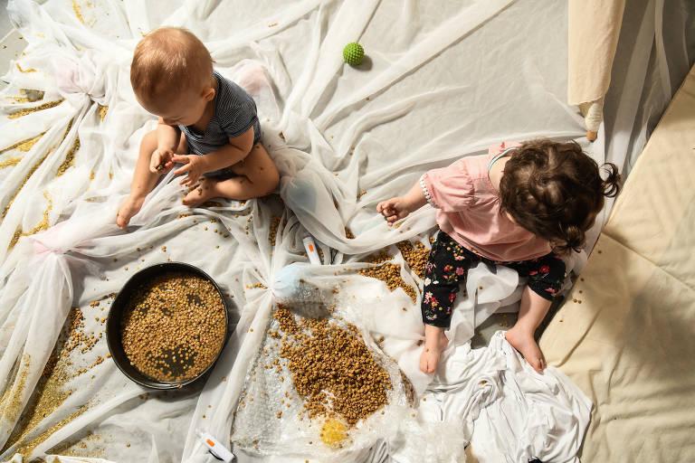 Crianças sentadas no chão mexendo em pote com lentilhas