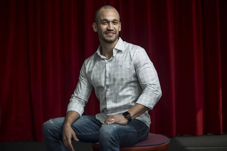 Homem de camisa social e jeans sentado
