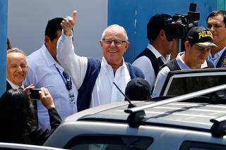 Peru's former President Pedro Pablo Kuczynski gestures while leaving the Institute of Legal Medicine and Forensic Sciences, after a local judge ordered his arrest, in Lima