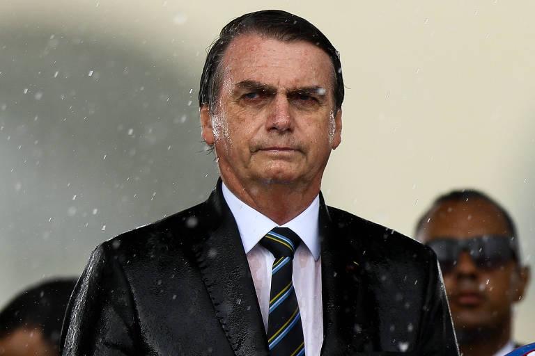 O presidente Jair Bolsonaro, sob chuva, em cerimônia de comemoração do Dia do Exército