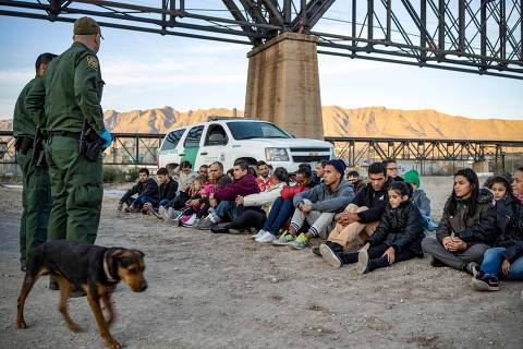 (FILES) In this file photo taken on March 20, 2019 a group of about 30 Brazilian migrants, who had just crossed the border, sit on the ground near US Border Patrol agents, on the property of Jeff Allen, who used to run a brick factory near Mt. Christo Rey on the US-Mexico border in Sunland Park, New Mexico. - The White House confirmed on April 14, 2019 it is looking at ways to transfer undocumented migrants to US sanctuary cities as Democrats accused President Donald Trump of creating