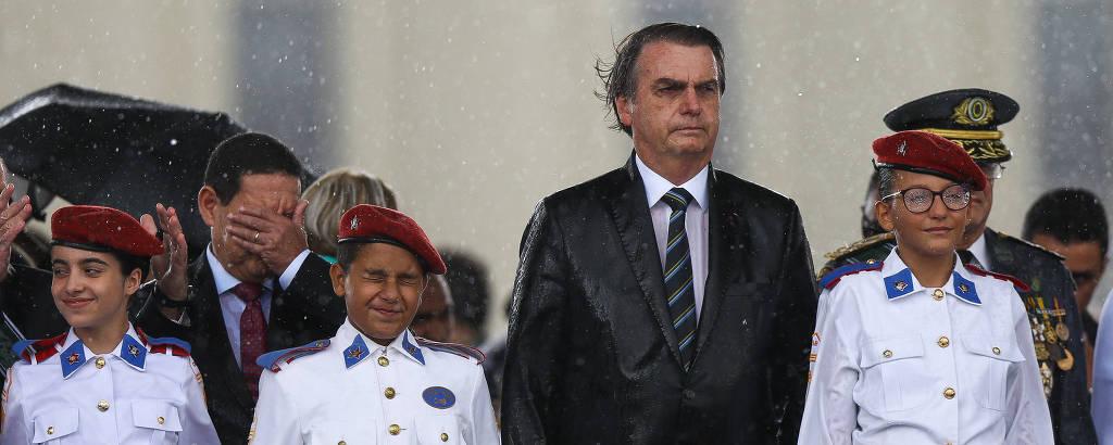Bolsonaro e o vice Mourão (com a mão no rosto) em cerimônia do Colégio Militar de Brasília