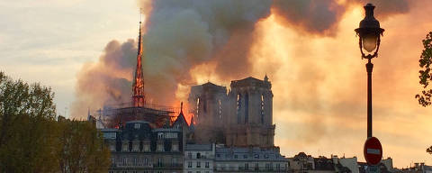 A picture taken with a mobile phone shows people looking at smoke and flames rising during a fire at the landmark Notre-Dame Cathedral in central Paris on April 15, 2019, potentially involving renovation works being carried out at the site, the fire service said. (Photo by Edouard MAGRINO / AFP)