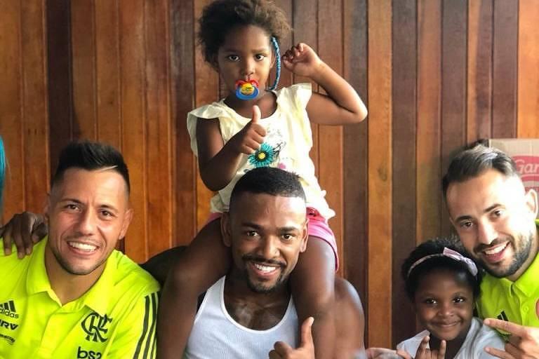 Nego do Borel e os jogadores do Flamengo Diego Alves e Everton Ribeiro dão presentes em comunidade