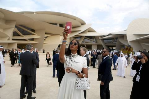 TOPSHOT - US model Naomi Campbell takes pictures upon her arrival to the inauguration ceremony of the National Museum of Qatar, designed by French architect Jean Nouvel, in the Gulf emirate's capital Doha, ahead of its official opening on March 27, 2019. - The complex architectural form of a desert rose, found in Qatar's arid desert regions, inspired the striking design of the new museum building, conceived by French architect Jean Nouvel. (Photo by Patrick BAZ / National Museum of Qatar / AFP) / == RESTRICTED TO EDITORIAL USE - MANDATORY CREDIT