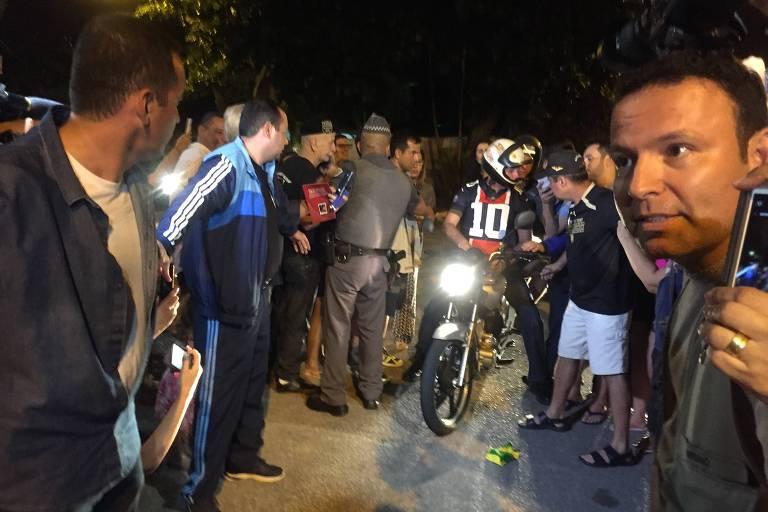 O presidente Jair Bolsonaro (de capacete) pilota moto em Guarujá (SP)