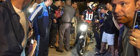 O presidente Jair Bolsonaro (de capacete) pilota moto em Guarujá (SP), onde passa o feriado prolongado de Páscoa