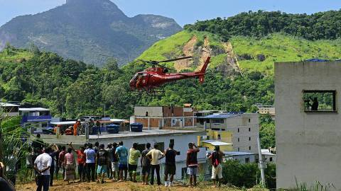 People watch a rescue helicopter as it flies away carrying an injured person after two buildings collapsed in Muzema, Rio de Janeiro, Brazil, on April 12, 2019. - At least two people were killed Friday when two buildings collapsed in a hillside neighborhood west of Rio de Janeiro, a region hard hit by heavy rain and flash floods in the past days, firefighters said. (Photo by CARL DE SOUZA / AFP) ORG XMIT: 1263