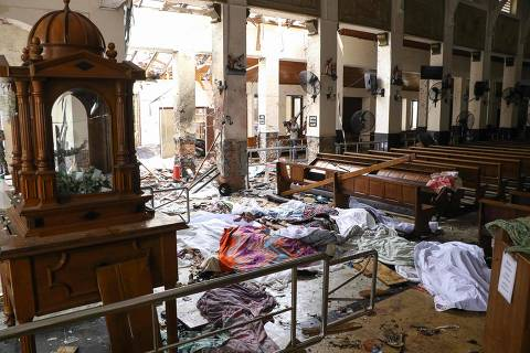 TOPSHOT - EDITORS NOTE: Graphic content / Sri Lankan security personnel walk past dead bodies covered with blankets amid blast debris at St. Anthony's Shrine following an explosion in the church in Kochchikade in Colombo on April 21, 2019. - A string of blasts ripped through high-end hotels and churches holding Easter services in Sri Lanka on April 21, killing at least 156 people, including 35 foreigners. (Photo by ISHARA S. KODIKARA / AFP) ORG XMIT: IK8377