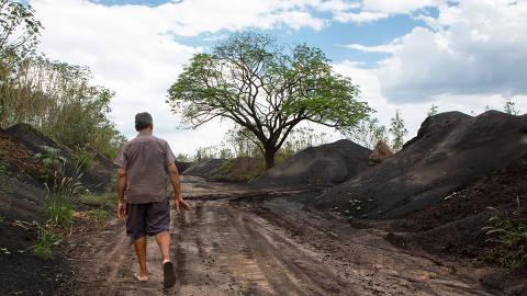 Senhor caminhando de costas:  Antônio Araújo, morador de Açailândia, caminha ao lado das montanhas de resíduos inflamáveis: não há cercas ou muros que impeçam o acesso dos moradores ao local Foto: Fernando Martinho/Repórter Brasil