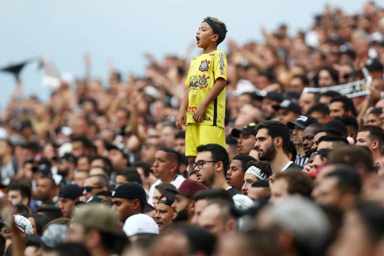Criança com roupa amarela em destaque, em pé, no meio de multidão