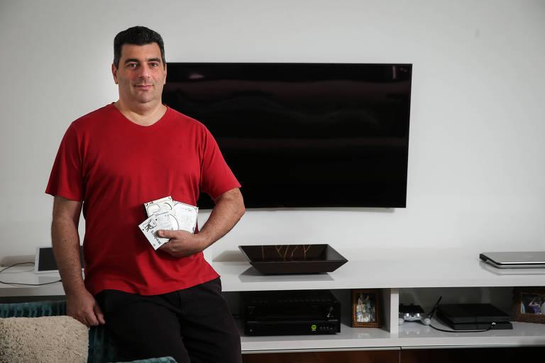 O engenheiro Fabio Romanini segura HDs queimados, ao lado de TV que já foi danificada por alterações no fornecimento de eletricidade