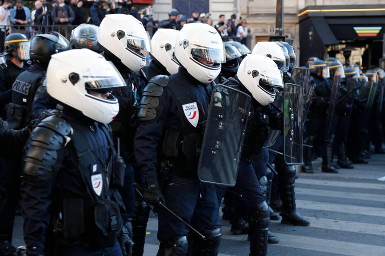 Policiais vestindo capacetes em linha