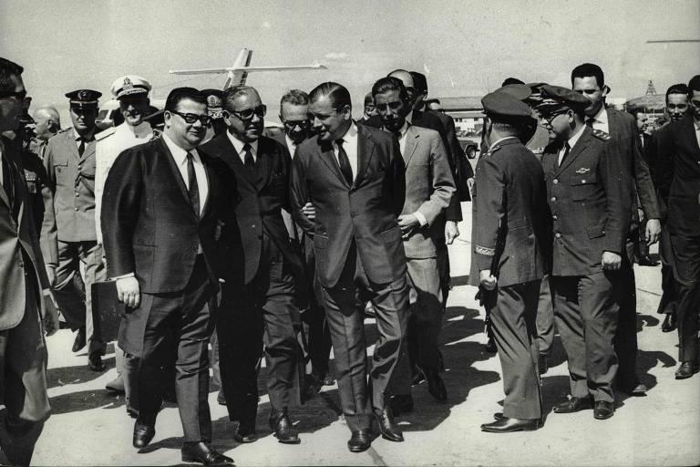 De braços dados com o governador Abreu Sodré (à dir.) e o ministro Delfim Netto (Fazenda), o presidente Arthur da Costa e silva caminha pela ala oficial de Congonhas.