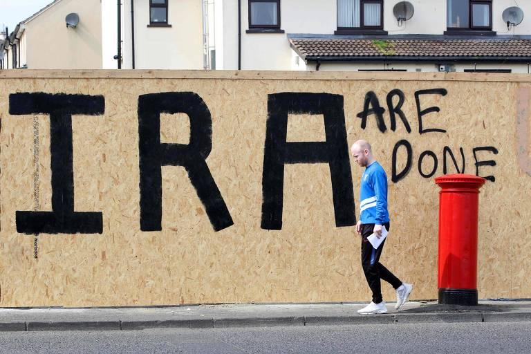 """Homem passa por mural com a inscrição """"o IRA está acabado"""" em local próximo onde a jornalista Lyra McKee foi morta em Londonderry"""