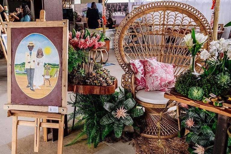 Decoração de Mara Perez mescla flores com objetos como cadeira e quadro e balaios
