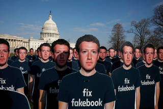 FILE PHOTO: Dozens of cardboard cutouts of Facebook CEO Mark Zuckerberg are seen during an Avaaz.org protest outside the U.S. Capitol in Washington