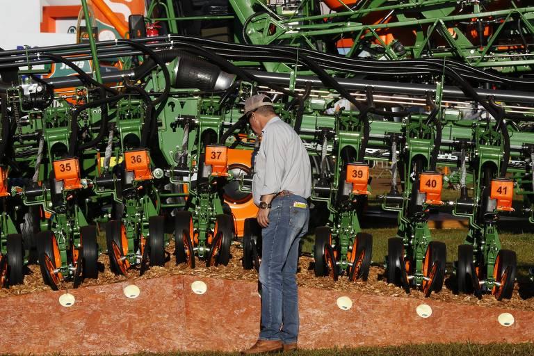 Homem usando chapéu observa máquinas agrícolas na edição de 2018 da Agrishow