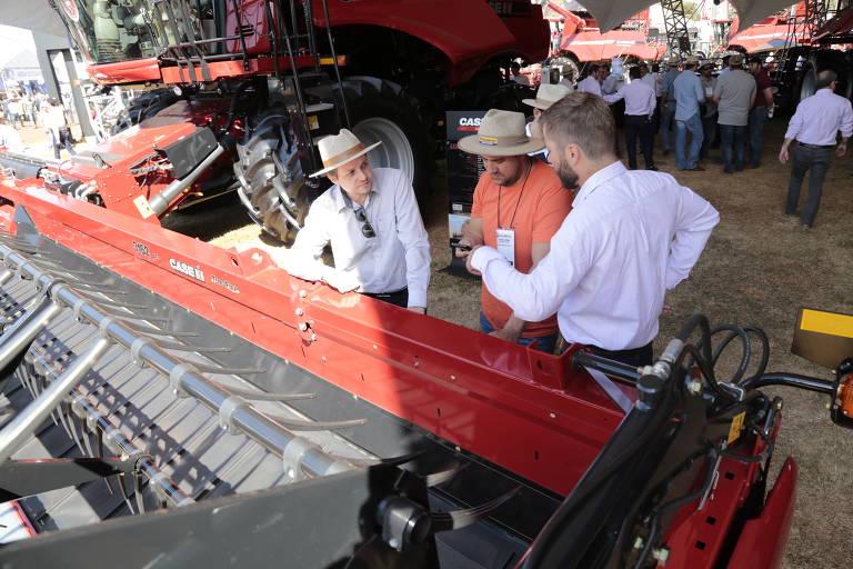 Três homens usando chapéu conversam ao lado de grande trator vermelho, há mais tratores ao fundo