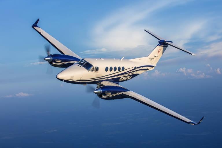 Avião turbo-hélice branco voando, com o céu azul ao fundo