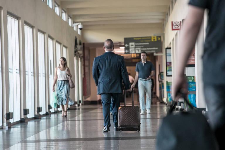 Homem de terno de costas carrega mala de rodinhas e outras pessoas passam em um corredor de aeroporto