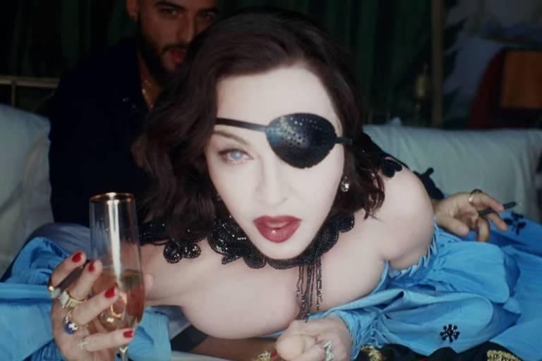 Madonna, com um tapa-olho, segura uma taça de champanhe na cama com Maluma