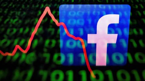 (FILES) This file illustration picture taken on April 26, 2018 in Paris shows the logo of social network Facebook displayed on a screen and reflected on a tablet. - On Wednesday April 24, 2019 Facebook reported quarterly profit sank 51 percent from a year earlier due to setting aside $3 billion for an anticipated fine from US regulators. (Photo by Lionel BONAVENTURE / AFP)