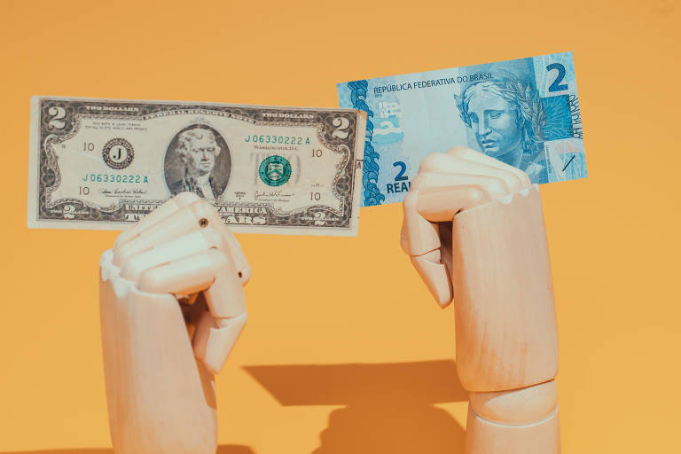 Retrato de duas mãos de madeira; uma segura uma nota de dólar, outra de real