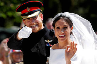 FILE PHOTO: Britain's Prince Harry gestures next to his wife Meghan as they ride a horse-drawn carriage after their wedding ceremony at St George's Chapel