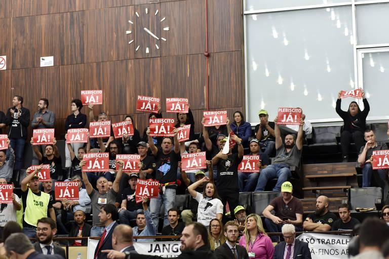 Pessoas em plenário seguram placas vermelhas com a frase Plebiscito já