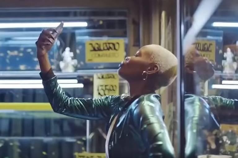 Mulher negra, com cabelos curtinhos. Ela usa uma jaqueta verde brilhante. Na cena, ela está fazendo uma selfie com o celular