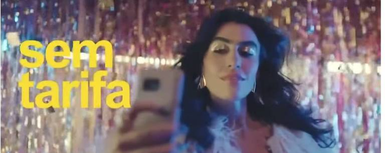 Mulher transexual faz selfie com o celular. No fundo, há uma parede com brilhos. Ela tem cabelos longos e pretos, pele clara e usa maquiagem dourara nos olhos