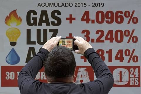 A man takes a snapshot of a banner placed by the Argentinian bank workers union showing how much public services fares have increased since the beginning of the government of Argentina's President Mauricio Macri and calling a strike for next April 30 at the financial district in Buenos Aires, on April 25, 2019. - Since his election in 2015, the market-friendly former Buenos Aires mayor has launched important economic reforms to balance years of spending by the previous leftist government of Cristina Kirchner -- but his promises to defeat inflation and place Argentina on the path to sustained growth have proved empty. (Photo by JUAN MABROMATA / AFP) ORG XMIT: MAB1082