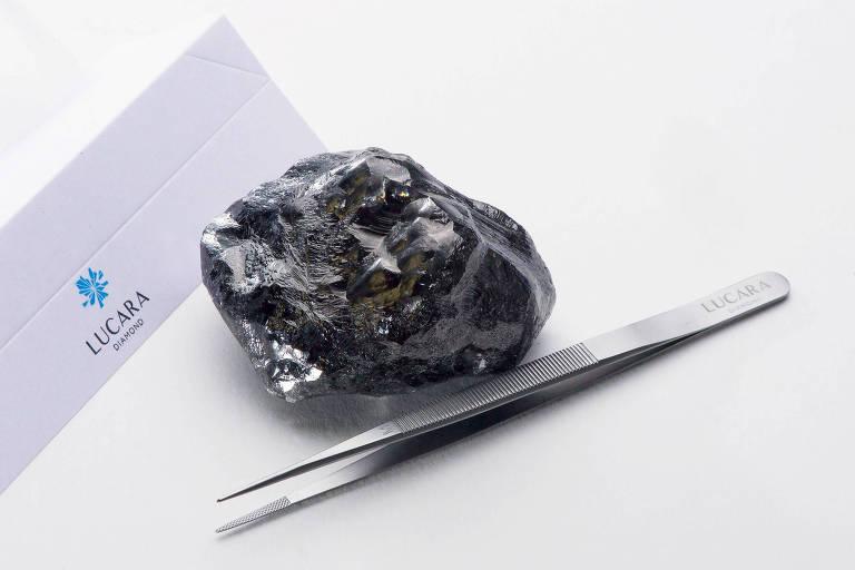 O segundo maior diamante do mundo está sob uma mesa branca, ao lado de uma pinça, à frente de uma caixa branca.