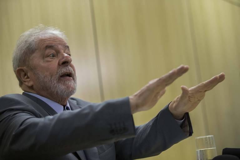 O ex-presidente Lula, com os braços para frente, em entrevista na Policia Federal em Curitiba, onde está preso