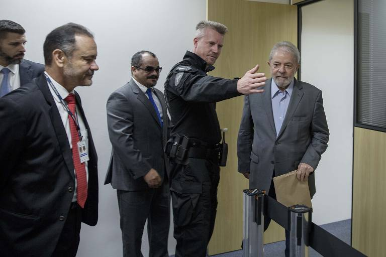 O agente da Polícia Federal Jorge Chastalo Filho escolta o ex-presidente Lula a caminho de entrevista para a Folha