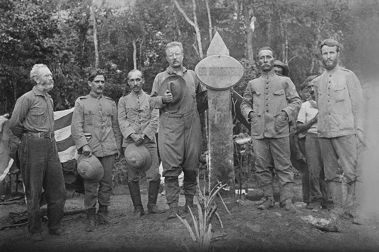 O ex-presidente norte-americano Theodore Roosevelt (à esq. da placa), marechal Rondon (à dir.) e membros de equipe expedicionária pelo rio Roosevelt