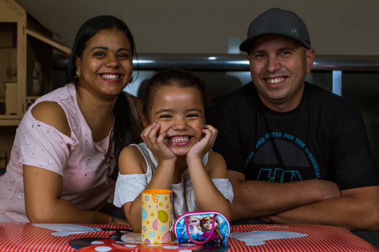 Criança de cinco anos sorri atrás do cofre e da bolsinha de dinheiro que ganhou dos pais, também na foto