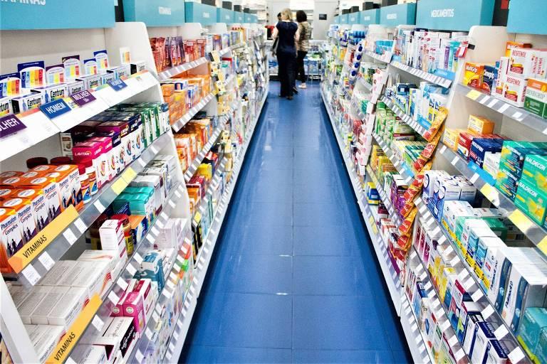 Duas estantes cheias de medicamentos e um corredor entre elas