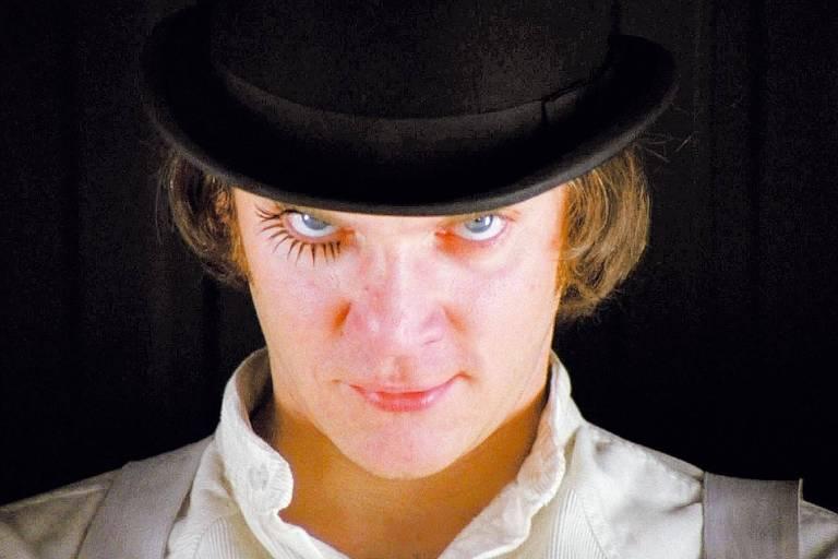 O ator Malcolm McDowell em cena do filme 'Laranja Mecânica' (1971), dirigido por Stanley Kubrick. Ele usa chapéu coco preto. Seu rosto está levemente inclinado para baixo, seus olhos azuis claros olhando para cima. Tem cabelo castanho claro cobrindo as orelhas. Tem pele branca, veste camisa branca e suspensório cinza. Um de seus olhos está maquiado.
